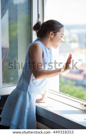 smiling teen girl wave with hand on window side shot - stock photo