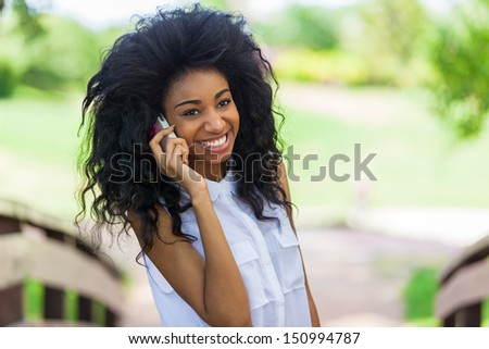 Smiling teenage black girl using a mobile phone  - African people - stock photo