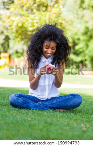 Smiling teenage black girl using a phone, sitting on the grass - African people - stock photo