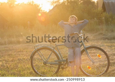 Smiling teenage cyclist in a relaxing pose - stock photo
