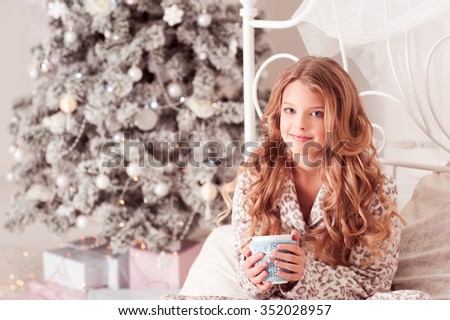 Smiling teenage girl holding cup of tea in room. Christmas tree. Looking at camera.  - stock photo
