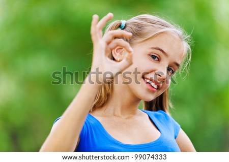 Smiling teenage girl in blue dress shows hand sign that she is doing fine, against background of green summer park. - stock photo