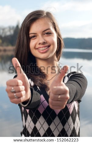 Smiling teenage girl picks up big thumbs up, against green of summer park. - stock photo