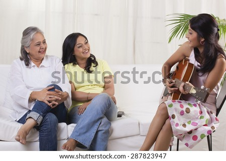 Smiling teenage girl playing guitar for her mother and grandmother - stock photo