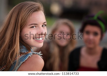 Smiling teenage girl with pair of female friends outdoors - stock photo