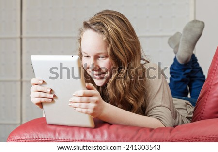 Smiling teenager girl lying on sofa with tablet computer - stock photo