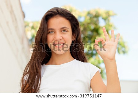 Smiling teenager girl saying ok outside - stock photo