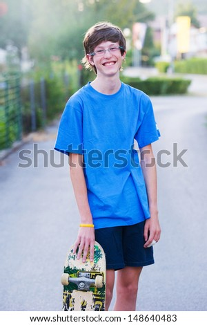 Smiling teenager holding his skateboard - stock photo