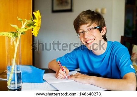 Smiling teenager studying and doing his homework while holding his pen and writing in his notebook.  - stock photo