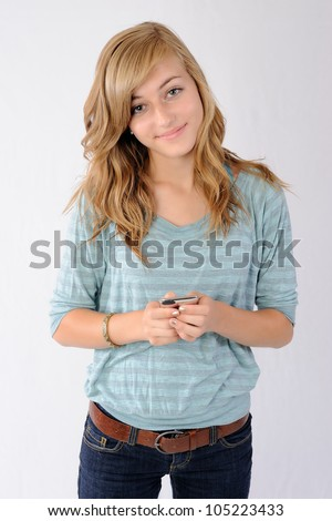 Smiling Teenager with Smartphone. Happy thirteen year old girl smiling at the viewer while holding a smartphone device. Note: Not Isolated. - stock photo