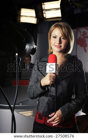 smiling television news reporter in live transmission with braking news in studio - stock photo