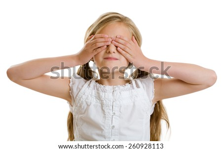 Smiling ten year old girl covering her eyes. - stock photo