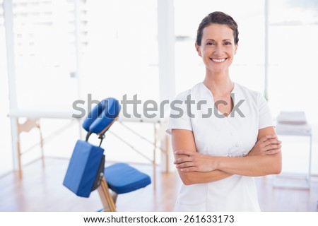 Smiling therapist standing with arms crossed in medical office - stock photo