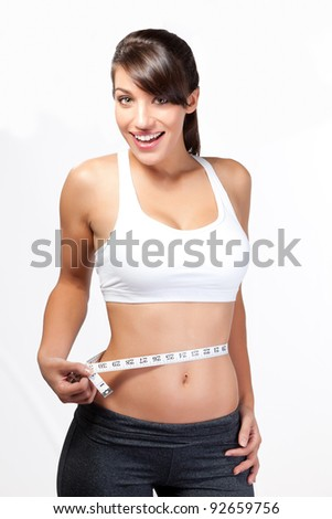 Smiling thin woman measuring waist - stock photo
