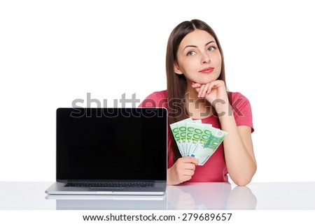 Smiling thinking woman showing laptop computer screen holding euro money in hand looking away at blank copy space, isolated on white background - stock photo