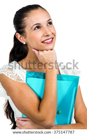 Smiling thoughtful woman holding plastic folder with fist on chin on white screen - stock photo