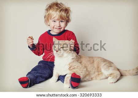 Smiling toddler boy with his pet cat. Vintage toned image. Focus on cat's face. - stock photo