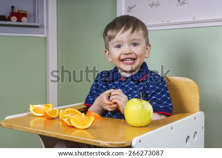 Smiling toddler eating fruit - stock photo