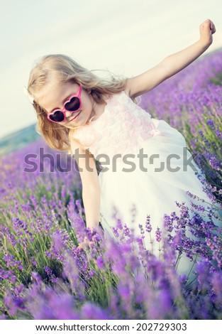 Smiling toddler girl in lavender field - stock photo
