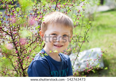 Smiling toddler posing by a cherry tree - stock photo