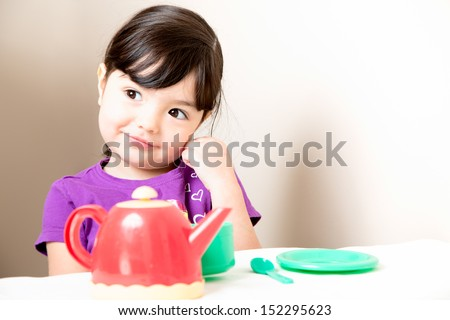 Smiling toddler thinking with relaxing a cup of tea - stock photo