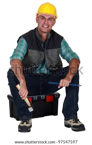 Smiling tradesman sitting on his toolbox and holding tools - stock photo