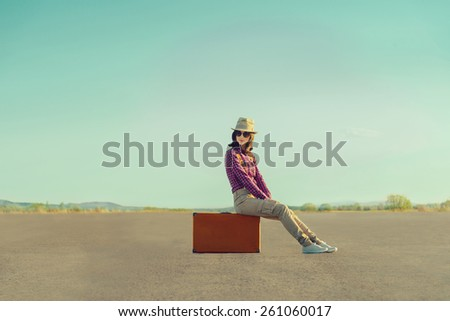 Smiling traveler girl in hat and sunglasses sitting on suitcase on road in summer - stock photo