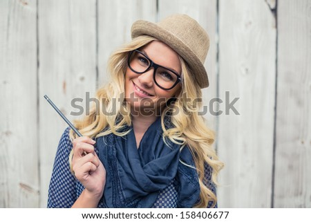 Smiling trendy blonde holding pencil on wooden background - stock photo
