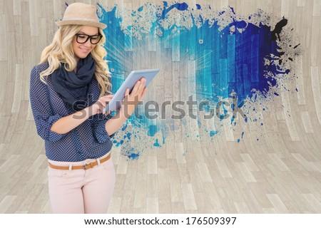 Smiling trendy blonde using tablet computer against splash showing blue light - stock photo