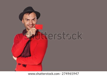 Smiling trendy casual man in red sweater and black hat showing blank credit card  - stock photo