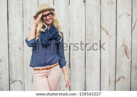 Smiling trendy model posing on wooden background - stock photo