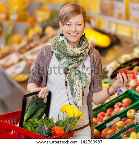 Smiling trendy young woman shopping for fresh produce holding a basket of vegetables and tulips in one hand and a fresh apple from the display in the other - stock photo