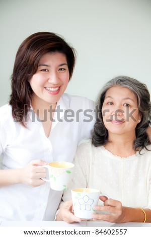 smiling two asian women holding their cups - stock photo