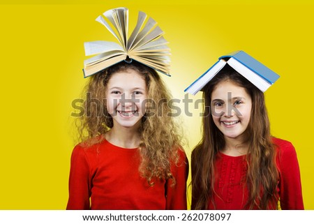 Smiling  Two sisters , little schoolgirl  with book on their head, isolated over yellow background.  - stock photo