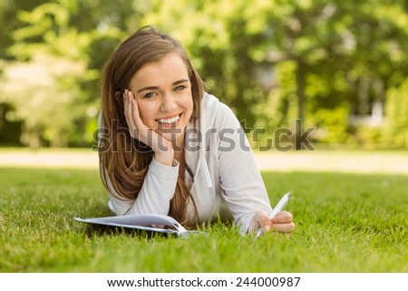 Smiling university student lying and writing on notepad in park at school - stock photo