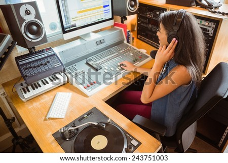 Smiling university student mixing audio in the studio of a radio - stock photo