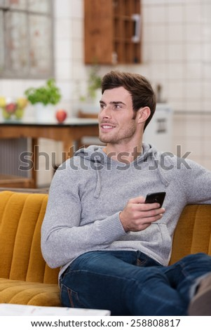 Smiling unshaven handsome young man relaxing at home on a couch with a mobile phone in his hand looking to the side - stock photo