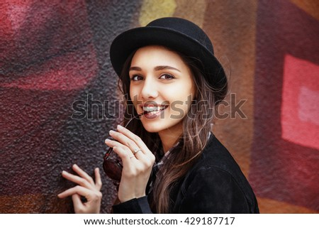 Smiling urban girl with smile on her face. Portrait of fashionable  gir wearing a rock black style having fun outdoors in the city - stock photo