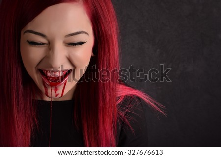 Smiling vampire woman with blood on her face - stock photo