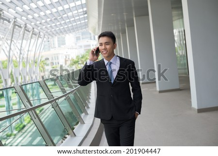 Smiling Vietnamese businessman talking on the phone in the office building - stock photo