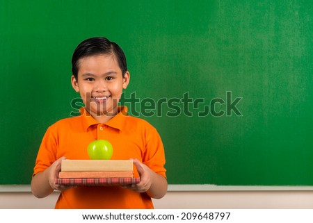 Smiling Vietnamese schoolboy holding books and a green apple - stock photo
