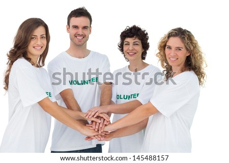Smiling volunteer group piling up their hands on white background - stock photo