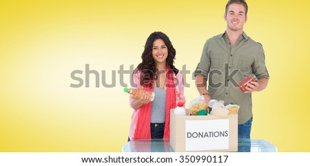 Smiling volunteers taking out food from donations box against yellow vignette - stock photo