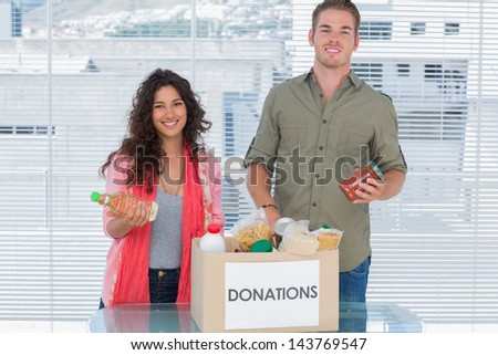 Smiling volunteers taking out food from donations box for a charity - stock photo