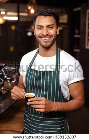Smiling waiter drinking a coffee at the coffee shop - stock photo