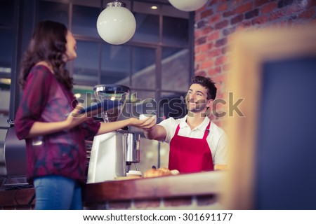 Smiling waiter serving a client at the coffee shop - stock photo