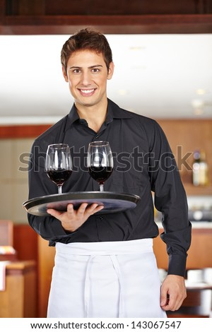 Smiling waiter serving red wine in a restaurant - stock photo