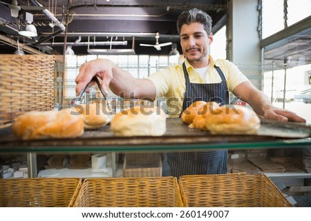 Smiling waiter taking bread with tongs at the bakery - stock photo