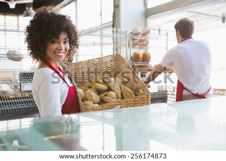 Smiling waitress carrying basket of bread at the bakery - stock photo