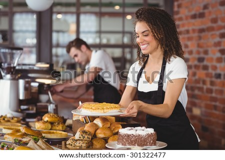 Smiling waitress holding cake in front of colleague at coffee shop - stock photo
